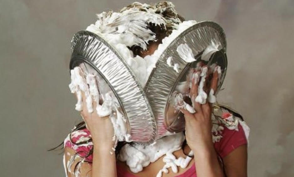 "alt=""Woman smashing two pies into her face"">"